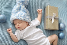 Cute Baby In Knitted Hat With Christmas Decor And Gift Box Sleeping On Blanket