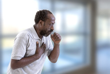 Portrait Of Afro-American Man Coughing, Throat Infection In A Bright Background