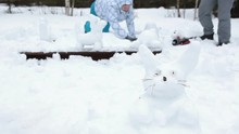 Rabbit From Snow On Foreground With People Making Snowman At Background, Winter