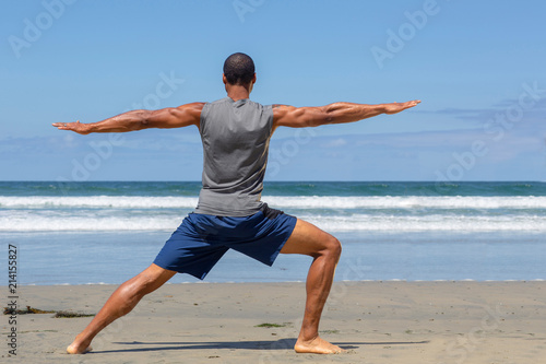 Fotografie, Obraz  Athletic man at the beach in Warrior ll yoga pose
