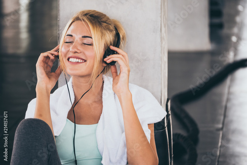 Young happy woman sitting and listening to music while having exercise break at the gym. - 214157671