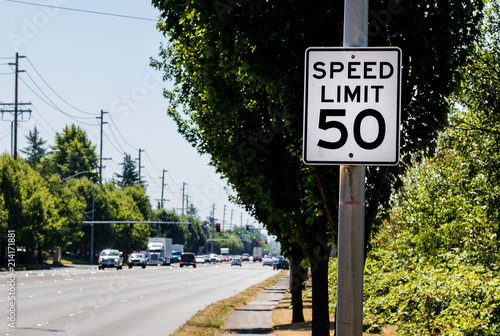 Fotomural 50 mph speed limit sign on post with a road and tree