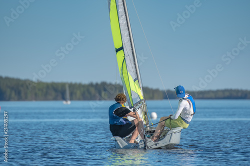 Photo Two young men are sailing on a calm lake with their 29er dinghy