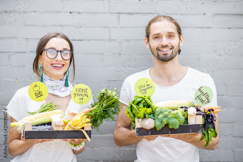 Young vegetarian couple standing with boxes full of fresh vegetables outdoors on the gray wall background