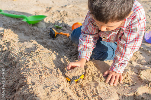 Photo  boy playing in the sand in summer