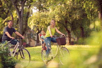 Smiling father and mother with kid on bicycles having fun in park..