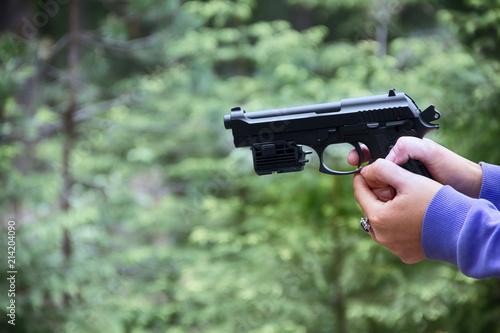 Fotografia, Obraz  Woman shoots from air gun in forest