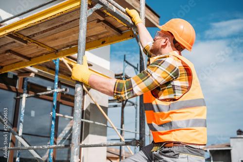 Fototapeta handsome builder climbing on scaffolding at construction site