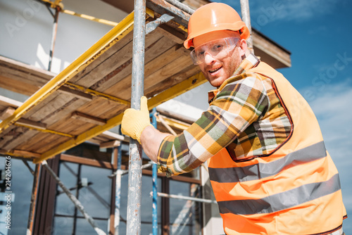 Obraz na plátně handsome builder climbing on scaffolding at construction site and looking at cam