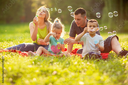 Poster Attraction parc Happy family with children blow soap bubbles outdoor.
