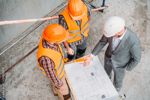 high angle view of builders and architect discussing blueprint at construction s Fotobehang