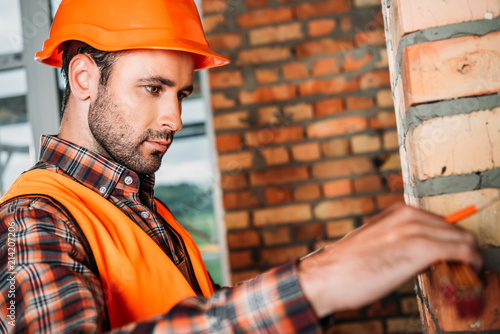 handsome young builder doing measurements at construction site