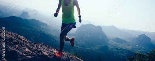 Fotografie, Tablou  woman running on mountain top cliff edge