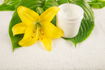 Obraz na płótnie Canvas yellow lily, green leaf, cream on white towel, spa salon