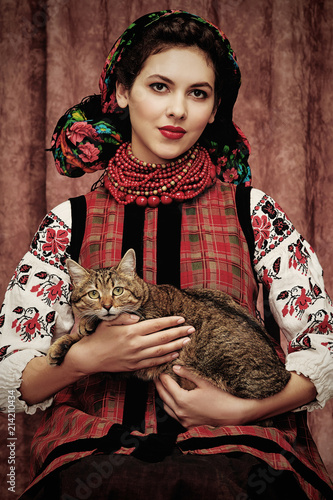 Three quarter isolated portrait of a young Slavic woman in ethnic costume, wearing embroidered blouse, floral head scarf, red bead necklace, holding a cat on her lap, posing on dark brown background.