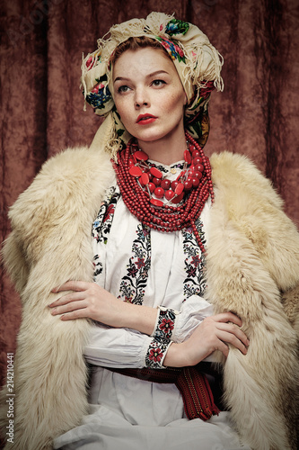 Fotografia Three quarter isolated studio portrait of a young beautiful Slavic woman in ethnic costume, wearing embroidered blouse, fur coat, floral head scarf, red bead necklace, posing on dark brown background