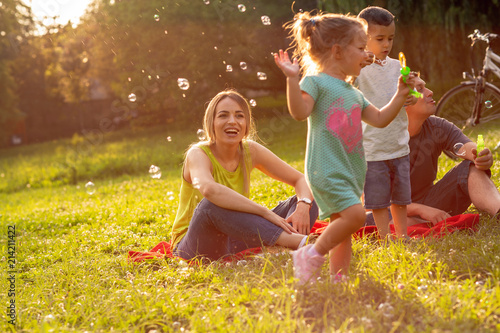 Obraz family, parenthood, adoption and people concept – Happy family with children blow soap bubbles in park. - fototapety do salonu