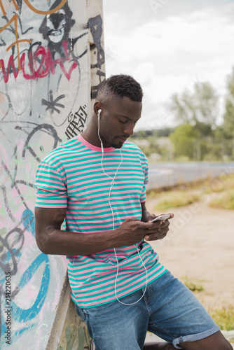 Foto op Aluminium Graffiti Young man in skatepark leaning against graffiti wall, listening music