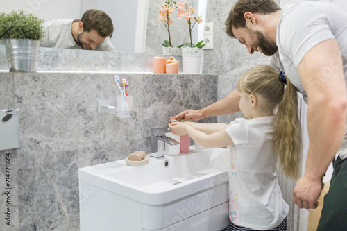 Fahtehr helping his little daughter washing her hands