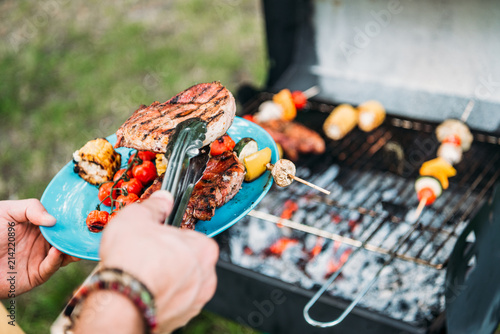 partial view of man wit tongs putting grilled food on plate during bbq in park Fototapet