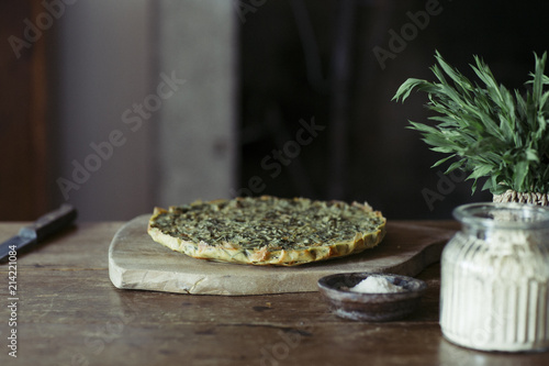 Homemade chickpea and herb cake on wooden table