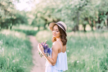 Pretty Woman Beautiful Young Happy With Long Dark Hair In White Dress And Hat Holding Small Bouquet Of Flowers, Nature Background Outdoors