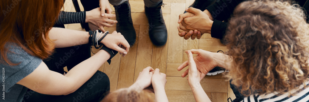 Fototapeta High angle view of hands of people in group therapy, talking and supporting each other
