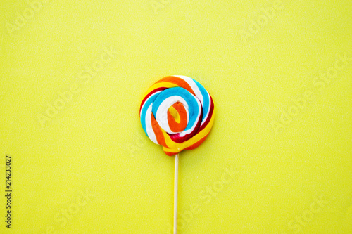Keuken foto achterwand Snoepjes Colorful hard candy lollipop on yellow pastel background. Rainbow sweet pattern on stick flying around. Christmas holiday design concept elements.