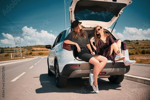 Fotografia, Obraz Two girls sitting in the trunk and talking