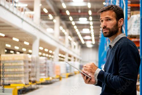 Obraz Manager in warehouse holding digital tablet - fototapety do salonu