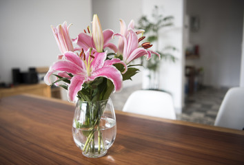 Bouquet pink lily flowers in glass vase on wood table in room.