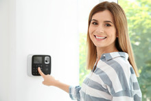 Young Woman Entering Code On Alarm System Keypad Indoors