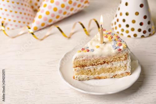 Slice of delicious birthday cake with candle on table