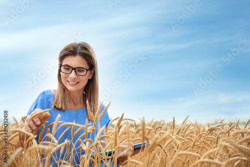 Fototapeta Young agronomist with clipboard and notebook in grain field. Cereal farming obraz