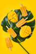 canvas print picture Mango popsicles over green tropical palm leaf on yellow colored background. Minimal flat lay style. Overhead, top view
