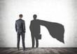 Leinwandbild Motiv Businessman looking at his superman shadow
