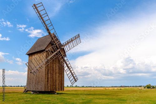Old wooden windmill on field in summer day. Poland