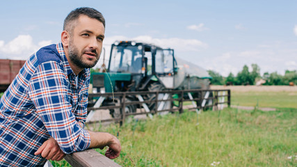 handsome middle aged farmer leaning at fence and looking away at farm