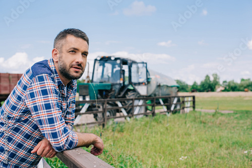 Foto pensive middle aged farmer leaning at railing and looking away at farm