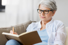 Age, Leisure And People Concept - Close Up Of Senior Woman In Glasses Writing To Notebook Or Diary At Home