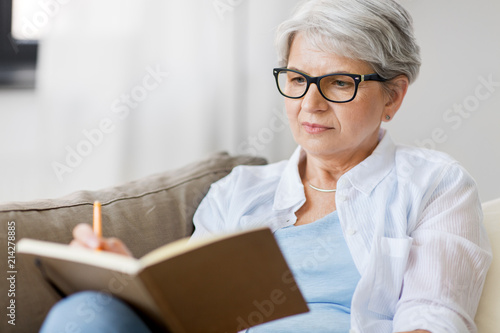 Obraz age, leisure and people concept - close up of senior woman in glasses writing to notebook or diary at home - fototapety do salonu