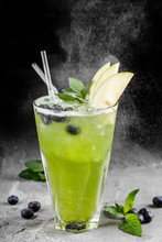 Fresh Green Apple Lemonade With Blueberries And Ice In Glass Over Dark Background. Summer Drinks And Cocktails.
