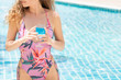 Happy young woman in swimsuit at swimming pool.