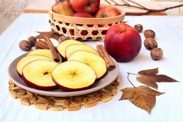 Naklejka na ściany i meble Round sliced apple with honey, fall leaves and nuts, on a veranda table, autumn still life.