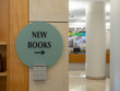 New books sign pointing to the right with library in background