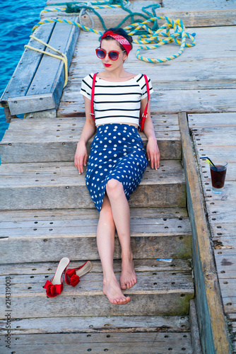 A girl on a wooden pier is waiting for a ship