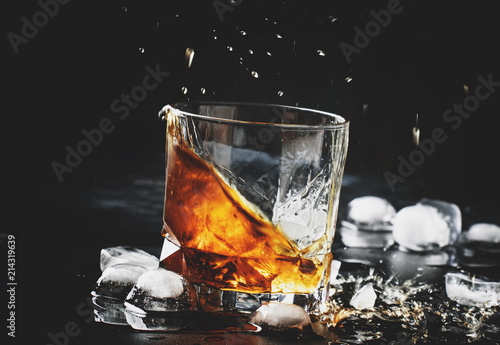 Whiskey with ice, splashes out of glass, dark background, toned image, selective focus