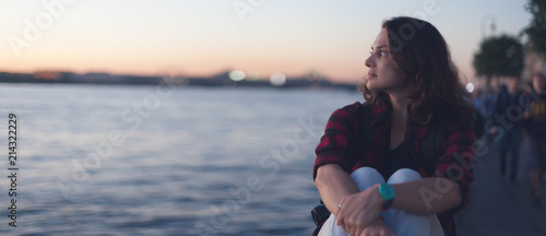 Fotografie, Obraz  Beautiful young girl sits on the river embankment and looks at the sunset