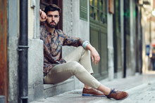 Young Bearded Man, Model Of Fashion, Sitting In An Urban Step Wearing Casual Clothes.