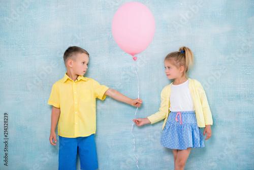 Obraz na plátně Boy child gives a balloon to a girl